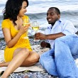 Happy couple having wine on beach - Stock Photo