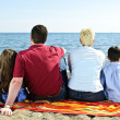 Family sitting at beach — Stock Photo