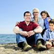 Happy family sitting at beach — Stock Photo