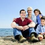 Happy family sitting at beach — Stock Photo