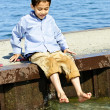 Boy playing on pier - Stock Photo