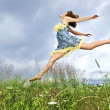 Stock Photo: Young girl jumping in meadow