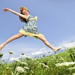 Young girl jumping in meadow — Stock Photo
