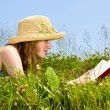 Stock Photo: Young girl reading book in meadow