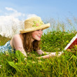 Young girl reading book in meadow — Stock Photo