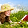 Young girl reading book in meadow — Stock Photo #4718863