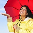 Beautiful young woman in raincoat with umbrella checking for rain - Foto Stock