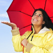 Beautiful young woman in raincoat with umbrella checking for rain - Photo