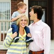 Happy family in front of home — Stock Photo #4719071