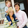 Happy family in front of home — Stock Photo #4719072