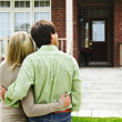 Happy couple in front of home — Stockfoto