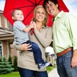 Happy family with umbrella - Stock Photo