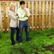 Couple concerned about lawn - Stock Photo
