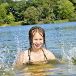 Girl splashing in lake - Stock Photo