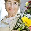 Elderly woman with flowers — Stock Photo #4719333