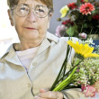 Elderly woman with flowers — Stock Photo #4719334
