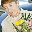 Stock Photo: Sad elderly womwith flowers
