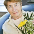 Elderly woman with flowers — Stock Photo