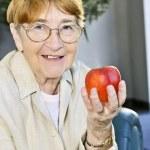 Elderly woman with apple — Stock Photo