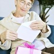 Old woman opening present — Stock Photo