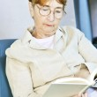 Old woman reading book — Stock Photo