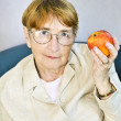 Elderly woman with apple — Stock Photo #4719376