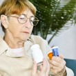 Elderly woman reading pill bottles — Stock Photo