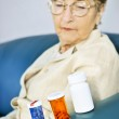 Elderly woman looking at pill bottles — Stock Photo