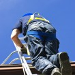 Construction worker climbing ladder — Stockfoto