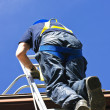 Стоковое фото: Construction worker climbing ladder