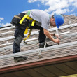 Man working on roof installing rails for solar panels — Foto Stock