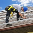 Foto Stock: Man working on roof installing rails for solar panels