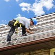 Man working on roof installing rails for solar panels - Stok fotoğraf