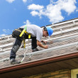 Man working on roof installing rails for solar panels - Stock Photo