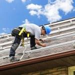 hombre trabajando en el techo, instalación de rieles para paneles solares — Foto de Stock