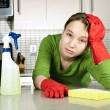 Tired girl cleaning kitchen - Stock Photo