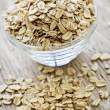 Bowl of raw rolled oats - Stock Photo