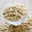 Bowl of uncooked rolled oats - Stock Photo