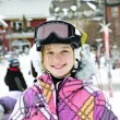 Stock Photo: Happy girl in ski helmet at winter resort