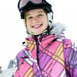 Happy girl in ski helmet at winter resort - Stock Photo