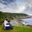 Children sitting at Atlantic coast in Newfoundland - Stok fotoğraf
