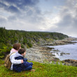 Children sitting at Atlantic coast in Newfoundland - Foto Stock