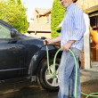 Man washing car on driveway - Stock Photo