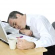 Businessman asleep at his desk on white background — Stock Photo #4719940