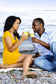 Happy couple having wine on beach — Stock Photo