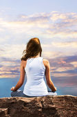Young girl meditating at sunset — Stock Photo