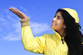 Beautiful young woman in raincoat checking for rain — Stock Photo