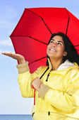 Beautiful young woman in raincoat with umbrella checking for rain — Stock Photo
