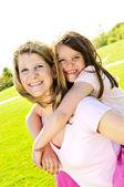 Mother and daughter piggyback — Stock Photo