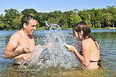 Family splashing in lake — Stock Photo